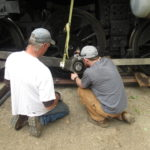 Charlie and Forest make small adjustments to center the rod over the crank pin so they can insert the bushing.